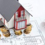 Haus auf Münzen und Grundriss - Symbolbild Fertighaus-Baufinanzierung