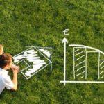Paar malt mit Kreide auf Rasen. Eine Kurve zeigt die Fertighaus Kosten an