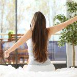 Gesund Wohnen und Schadstoffe vermeiden: Frau streckt sich beim Aufwachen