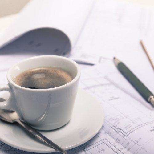 Bebauungspläne mit Kaffeetasse und Stift