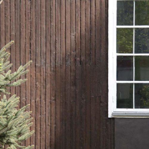 Ausschnitt aus Holzhaus mit Fenster und Tanne - was ist besser? Holzhaus vs. Massivhaus